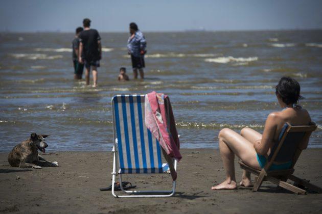 Gente en el mar y otras en reposeras